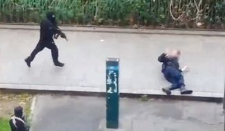 Cell phone footage captures the moment two gunmen shoot and kill a police officer on a Paris street during an attack on magazine Charlie Hebdo.