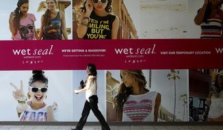 FILE - In this July 2, 2013 file photo, Shianne Penoli walks past the future location of Wet Seal at the Mt. Shasta Mall in Redding, Calif.  Wet Seal is closing 338 of its stores, resulting in nearly 3,700 full and part-time workers losing their jobs. The retailer said that it decided to proceed with the store closures after looking at its overall financial condition and wasn't able to negotiate meaningful concessions from landlords. The closures are effective Wednesday, Jan. 7, 2015. (AP Photo/Record Searchlight, Greg Barnette)
