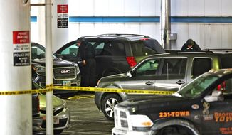 Members of the bomb squad check out a parked SUV at port Columbus Airport on Wednesday, Jan. 7, 2015, after police shot a man in Columbus, Ohio. A man who tried to buy an airline ticket using a fake ID was fatally shot Wednesday after returning to his illegally parked car, where he lunged at an airport police officer with a knife during a confrontation, police said.  (AP Photo/The Columbus Dispatch, Chris Russell)