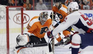 Philadelphia Flyers' Steve Mason, left, blocks a shot by Washington Capitals' Mike Green, right, during the first period of an NHL hockey game, Thursday, Jan. 8, 2015, in Philadelphia. (AP Photo/Matt Slocum)