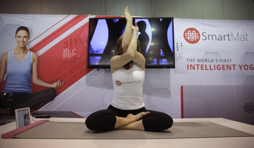 FILE - In this Jan. 7, 2015 file photo, a model exercises on the SmartMat, an intelligent yoga mat, at the SmartMat booth at the International CES in Las Vegas. SmartMat costs $297 and will ship in July. (AP Photo/Jae C. Hong)