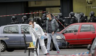 SWAT police officers, background, arrive after a shooting in Montrouge, outside Paris, Thursday, Jan. 8, 2015. An assailant opened fire on a police officer on the southern edge of Paris early Thursday, killing her and injuring a nearby street sweeper before fleeing, officials and a witness said. France's interior minister cautioned against jumping to conclusions a day after the deadly assault on a satirical newspaper that killed 12 people.  (AP Photo/Christophe Ena)