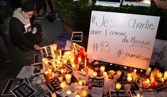 """A woman lights a candle on a makeshift alter including signs that read in French """"I am Charlie"""" during a vigil in solidarity with those killed in an attack at the Paris offices of the weekly newspaper Charlie Hebdo, outside France's embassy in Mexico City, Thursday, Jan. 8, 2015. Masked gunmen stormed on Wednesday the weekly newspaper that caricatured the Prophet Muhammad, killing at least 12 people, including the editor, before escaping in a car. It was France's deadliest postwar terrorist attack. (AP Photo/Marco Ugarte)"""