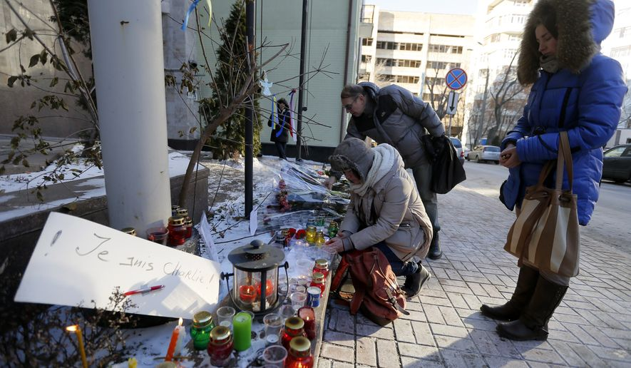 """People light a candle outside the French Embassy in Kiev, Ukraine, Thursday, Jan. 08, 2015. French President Francois Hollande says the country has been """"struck in the heart"""" of its capital city in the attacks on a satirical newspaper. Masked gunmen stormed the offices of Charlie Hebdo on Wednesday, killing 12 people inside and out before fleeing. (AP Photo/Sergei Chuzavkov)"""