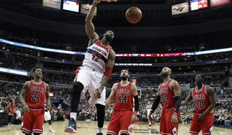 Washington Wizards forward Nene (42), from Brazil, dunks the ball in front of Chicago Bulls guard Jimmy Butler (21), forward Nikola Mirotic (44), from Montenegro, forward Taj Gibson (22) and forward Tony Snell (20) in the first half of an NBA basketball game, Friday, Jan. 9, 2015, in Washington. The Wizards won 102-86. (AP Photo/Alex Brandon)