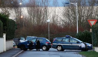 French security officers take cover behind vehicles as they surround a building in Dammartin-en-Goele, northeast of Paris, where the two brothers suspected in a deadly terror attack were cornered, Friday, Jan. 9, 2015. Explosions and gunshots rang out and smoke rose outside a building where two brothers suspected in a newspaper massacre are holed up with a hostage. (AP Photo/Thibault Camus)