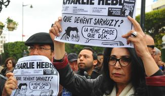 Tunisians hold up old copies of Charlie Hebdo on the iconic Bourguiba Avenue in Tunis, Tunisia, during a gathering in solidarity with those killed in an attack at the Paris offices of the weekly newspaper Charlie Hebdo, Friday, Jan. 9, 2015. Two sets of attackers seized hostages and locked down hundreds of French security forces around the capital on Friday, sending the city into fear and turmoil for a third day in a series of linked attacks that began with the deadly newspaper terror attack that left 12 people dead. (AP Photo/Hassene Dridi)