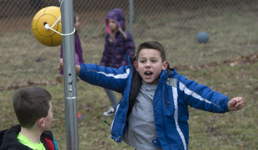Austin Bryant celebrates his victory at tether ball with Hogan Conder during recess at Marlin Elementary School in Bloomington, Ind.