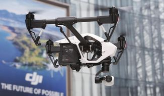 In this Monday, Dec. 15, 2014, photo, a DJI Technology Co.'s Inspire 1 drone flies against the backdrop of a DJI's advertisement board during a demonstration in Shenzhen, south China's Guangdong province. (AP Photo/Kin Cheung) ** FILE **