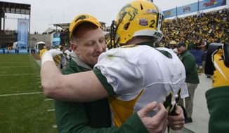 North Dakota State head coach Chris Klieman, left, hugs safety Colten Heagle (20) in the closing seconds of their FCS Championship NCAA college football game against the Illinois State, Saturday, Jan. 10, 2015, in Frisco, Texas. North Dakota State won the game 29-27 for their fourth straight national championship.  (AP Photo/Tim Sharp)