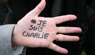 "Brigitte Le Blein, of Nice, shows her hand reading ""I am Charlie"" during a silent march for victims of the shooting at the satirical newspaper Charlie Hebdo, Saturday, Jan. 10, 2015, in Nice, southeastern France. Ten journalists and two policemen were killed on Jan. 7 in a terrorist attack at the Charlie Hebdo headquarters in Paris. (AP Photo/Lionel Cironneau)"