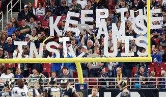 HOLD FOR STORY BY JIM SALTER - In this Nov. 30, 2014 photo, St. Louis Rams fans in the end zone spell out Keep The Rams In St Louis during an NFL football game against the Oakland Raiders at the Edward Jones Dome in St. Louis. St. Louis fans took another hit this week when Rams owner Stan Kroenke joined in a development group that plans an 80,000-seat stadium in the Los Angeles suburbs. Experts say losing an NFL team would have a small potatoes economic impact in St. Louis, but acknowledge that the blow to the region's psyche would be far greater. (AP Photo/St. Louis Post Dispatch, Chris Lee)