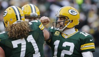 Green Bay Packers quarterback Aaron Rodgers (12) with guard Josh Sitton (71) celebrates a touchdown during the second half of an NFL divisional playoff football game against the Dallas Cowboys Sunday, Jan. 11, 2015, in Green Bay, Wis. (AP Photo/Nam Y. Huh)