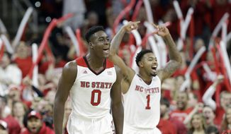 North Carolina State's Abdul-Malik Abu (0) and Trevor Lacey (1) react during the first half of an NCAA college basketball game against Duke in Raleigh, N.C., Sunday, Jan. 11, 2015. North Carolina State won 87-75. (AP Photo/Gerry Broome)