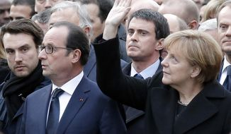 French President Francois Hollande, second from left, and German Chancellor Angela Merkel, right, join other dignitaries, heads of government and heads of state as they march during a rally in Paris, Sunday, Jan. 11, 2015. More than 40 world leaders, their arms linked, marched through Paris Sunday to rally for unity and freedom of expression and to honor 17 victims of three days of terrorist attacks. (AP Photo/Francois Mori)