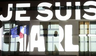 The words ' I am Charlie' are projected on the French embassy near Brandenburg Gate in Berlin after several thousand people gathered in solidarity with victims of two terrorist attacks in Paris, one at the office of weekly newspaper Charlie Hebdo and another at a kosher market.  (AP Photo/Markus Schreiber)