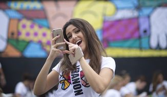 Miss Lebanon, Saly Greige, poses for photos after she painted on a wall in Miami's Wynwood area, Sunday, Jan. 11, 2015. Miss Universe contestants visited pop artist Romero Britto's studio for an interactive painting event. (AP Photo/J Pat Carter)