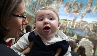 A woman holds a baby as Pope Francis, background, delivers his speech during a baptizing ceremony in the Sistine Chapel at the Vatican, Sunday, Jan. 11, 2015. Pope Francis on Sunday baptized 33 babies in the Sistine Chapel as part of an annual tradition, this year repeating an invitation to mothers to nurse their babies if crying out of hunger. (AP Photo/L'Osservatore Romano, pool)