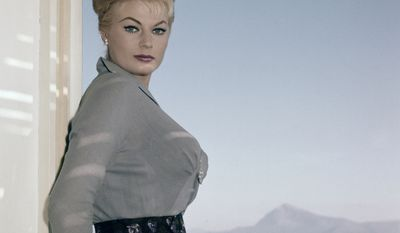 """In this Nov. 29, 1960 file photo, Swedish actress Anita Ekberg poses on the terrace of her hotel in Maratea, southern Italy. Anita Ekberg, the Swedish-born actress and sex-symbol of the 1950s and '60s who was immortalized bathing in the Trevi fountain in """"La Dolce Vita,"""" has died. She was 83. Ekberg's lawyer Patrizia Ubaldi confirmed her death Sunday, Jan. 11, 2015. (AP Photo/Mario Torrisi, file)"""