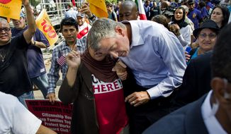 Bill de Blasio, Democratic nominee for New York mayor, leans over to listen to a woman after he spoke at a march and rally highlighting immigration reform Saturday, Oct. 5, 2013, in New York. (AP Photo/Craig Ruttle)