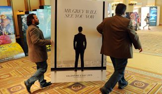 "Sheldon Domke, left, and Adam Mast move an advertisement for the upcoming film ""Fifty Shades of Grey"" during a Las Vegas convention in 2014. The film is set for release on Feb. 13. (Photo by Chris Pizzello/Invision/AP)"