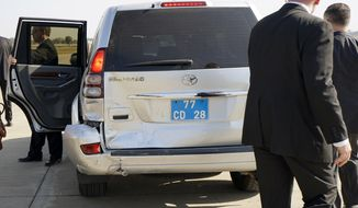 Diplomatic Security Service agents look at the crushed rear door of U.S. Secretary of State John Kerry's vehicle after his car was hit from behind by another vehicle while traveling to the airport in Ahmedabad, India, Monday, Jan. 12, 2015. The accident was caused by a driver further up in the motorcade suddenly braking for a puppy on a road. (AP Photo/Rick Wilking, Pool)