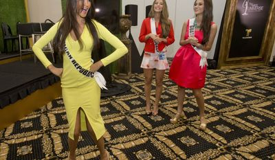 Miss Universe contestant Kimberly Castillo, of the Dominican Republic, dances as Alejandra Argudo, of Ecuador, center, and Ana Montufar Urrutia, of Guatemala, watch after a news conference for contestants from Latin America and Spain, Monday, Jan. 12, 2015, in Doral, Fla. The Miss Universe pageant will be held on Jan. 25, in Miami. (AP Photo/Wilfredo Lee)