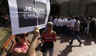 """Two women hold  """"Je Suis Charlie"""" (I am Charlie) signs during a gathering in solidarity with victims of the recent Paris terrorist attacks, at the Plaza de Francia in Panama City, Monday, Jan. 12, 2015. A group of foreign residents and Panamanian citizens gathered to protest against the recent terrorist attacks in France. (AP Photo/Arnulfo Franco)"""