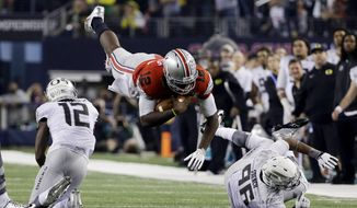 Ohio State's Cardale Jones (12) dives for a first down during the second half of the NCAA college football playoff championship game against Oregon Monday, Jan. 12, 2015, in Arlington, Texas. (AP Photo/David J. Phillip)