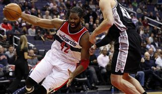 Washington Wizards forward Nene (42) drives against San Antonio Spurs center Tiago Splitter, both from Bazil, during the first half of an NBA basketball game, Tuesday, Jan. 13, 2015, in Washington. (AP Photo/Alex Brandon)