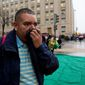 Reynaldo Hernandez holds a cloth over his face after being evacuated from a smoke filled Metro subway tunnel Monday that left one dead and sent dozens to the hospital. Authorities say the source of the smoke is unknown. (Associated Press)