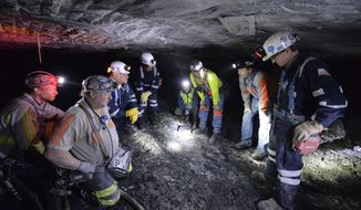 Joe Main, third from left, Assistant Secretary of Labor for Mine Safety and Health, and Patricia Silvey, center, Deputy Assistant Secretary for Operations with MSHA, speak with workers at the Gibson North mine, Tuesday, Jan. 13, 2015, in Princeton, Ind. Main and Silvey were being shown a new proximity sensor that will increase the safety of workers around mining machinery. (AP Photo/Timothy D. Easley)