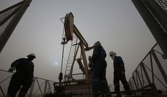 In this Jan. 8, 2015, file photo, men work on an oil pump during a sandstorm in the desert oil fields of Sakhir, Bahrain. The price of oil dipped below $45 a barrel Tuesday, Jan. 13, 2015, following the latest sign from OPEC that the group doesn't plan to cut production. (AP Photo/Hasan Jamali, File)