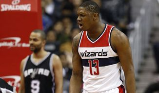 Washington Wizards center Kevin Seraphin (13), from France, reacts after a play with San Antonio Spurs guard Tony Parker, rear, frrom France, during the second half of an NBA basketball game, Tuesday, Jan. 13, 2015, in Washington. The Wizards won 101-93. (AP Photo/Alex Brandon)