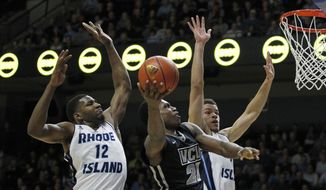 VCU guard Treveon Graham (21) has a shot blocked by Rhode Island forward Hassan Martin (12) as forward Jarelle Reischel, right, defends on the play during the first half of an NCAA college basketball game, Tuesday, Jan. 13, 2015, in Kingston, R.I. (AP Photo/Stew Milne)