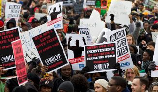 Demonstrators march on Pennsylvania Avenue toward Capitol Hill in Washington, Saturday, Dec. 13, 2014, during the Justice for All march. More than 10,000 protesters are converging on Washington in an effort to bring attention to the deaths of unarmed black men at the hands of police. Civil rights organizations are holding a march to the Capitol on Saturday with the families of Michael Brown and Eric Garner, two unarmed black men who died in incidents with white police officers. (AP Photo/Jose Luis Magana)