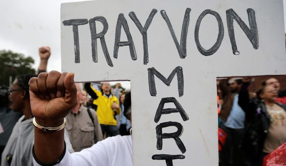 A protester carries a cross with the name of Trayvon Martin during a march to the Ferguson, Mo., police station Monday, Oct. 13, 2014, in Ferguson. (AP Photo/Charles Rex Arbogast) ** FILE **