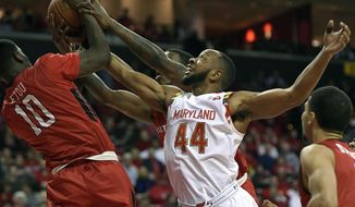 Maryland guard/forward Dez Wells (44) fights for the ball against Rutgers forward Junior Etou (10) during the second half of an NCAA college basketball game, Wednesday, Jan. 14, 2015, in College Park, Md. Maryland won 73-65. (AP Photo/Nick Wass)