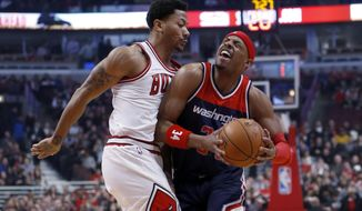 Washington Wizards forward Paul Pierce, right, reacts after being fouled by Chicago Bulls guard Derrick Rose (1) during the first half of an NBA basketball game Wednesday, Jan. 14, 2015, in Chicago. (AP Photo/Charles Rex Arbogast)