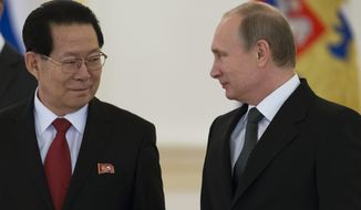In this Nov. 19, 2014 file photo, North Korea's new Ambassador to Russia Kim Hyun Joon, left, poses with Russian President Vladimir Putin for a photo after presenting his credentials from North Korean leader Kim Jong Un to Putin in the Kremlin in Moscow, Russia. (AP Photo/Alexander Zemlianichenko, Pool,File)
