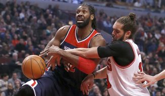 Washington Wizards forward Nene, left, is fouled by Chicago Bulls center Joakim Noah as Nene drives to the basket during the first half of an NBA basketball game Wednesday, Jan. 14, 2015, in Chicago. (AP Photo/Charles Rex Arbogast)
