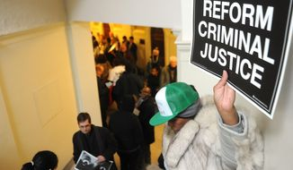 FILE - In this Jan. 7, 2015, file photo, a woman holds a sign in the Senate gallery during the opening of the Missouri legislature in Jefferson City, Mo., protesting the criminal justice and the fatal shooting of unarmed, black 18-year-old Michael Brown by a white police officer.  Police killings of unarmed residents in Missouri, New York and elsewhere have prompted an array of proposals from newly-convening state legislatures seeking to place greater scrutiny on the interactions between law officers and the public. (AP Photo/Columbia Daily Tribune, Don Shrubshell, File)