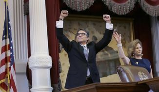 Texas Gov. Rick Perry, left, acknowledges applause next to his wife, Anita, before giving a farewell speech to a joint session of the Texas Legislature, Thursday, Jan. 15, 2015, in Austin, Texas. (AP Photo/Eric Gay)