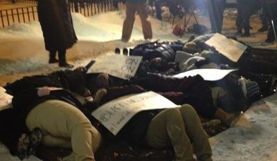 Protesters who argue the University of Chicago should spend its resources re-opening its trauma center instead of hosting the new Barack Obama Presidential Library hosted a die-in Tuesday night ahead of a public hearing on the issue. (Twitter/Jewish Council on Urban Affairs)