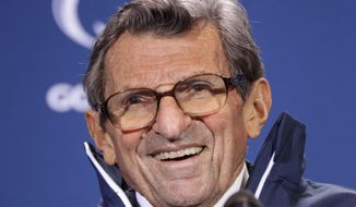 FILE - In this Oct. 29, 2011, file photo, Penn State head coach Joe Paterno smiles as he talks with reporters after recording his 409th career coaching victory, a 10-7 win over Illinois, during a a post-game NCAA college football news conference in State College, Pa.  A proposed settlement, announced Friday, Jan. 16, 2015, by the NCAA, will give Penn State back 112 football team wins that were vacated two years ago in the Jerry Sandusky child molestation scandal.  If approved, the new agreement also would restore former coach Paterno's status as the winningest coach in major college football history with 409 victories.  (AP Photo/Gene J. Puskar, File)