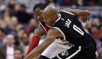 Washington Wizards guard John Wall (2) attempts to steal the ball from Brooklyn Nets guard Jarrett Jack (0) during the second half of an NBA basketball game, Friday, Jan. 16, 2015, in Washington. Jack maintained possession. The Nets won 102-80.(AP Photo/Alex Brandon)