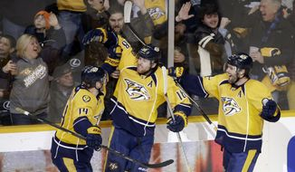 Fans react as Nashville Predators left wing James Neal (18) celebrates with teammates Mattias Ekholm (14), of Sweden, and Mike Fisher, right, after scoring the winning goal against the Washington Capitals in the third period of an NHL hockey game Friday, Jan. 16, 2015, in Nashville, Tenn. It was the second goal of the game for Neal and gave the Predators a 4-3 win. (AP Photo/Mark Humphrey)