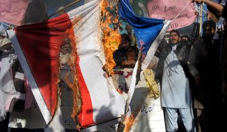 Pakistani protesters burn a representation of a French flag during a protest against  caricatures published in the French magazine Charlie Hebdo, in Peshawar,  Pakistan, Friday, Jan. 16, 2015. Pakistani students are clashing with police during protests against the French satirical magazine that was attacked last week for publishing images of the Prophet Muhammad. (AP Photo/Mohammad Sajjad)