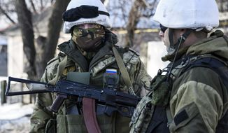 In this Thursday, Jan. 15, 2015, photo, pro-Russian rebels stand on guard near their position in the Donetsk airport in Donetsk, Eastern Ukraine. Russian-backed separatists announced Thursday they had captured the shattered remains of the Donetsk airport terminal and plan to claw back more territory, further dashing hopes for a lasting peace agreement. (AP Photo/Mstyslav Chernov)