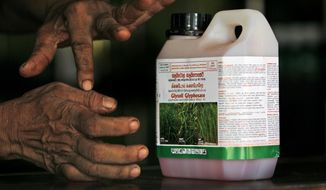 An agrochemical vendor gives instructions on how to use glyphosate, a popular weed killer. (Associated Press/File)